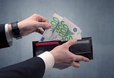 La mano in vestito elimina l'euro dal portafoglio Fotografie Stock Libere da Diritti