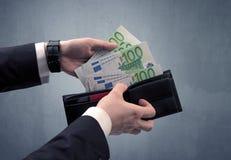 La mano in vestito elimina l'euro dal portafoglio Immagini Stock Libere da Diritti