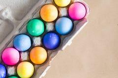 La mano vibrante teñió los huevos de Pascua coloridos en una caja Fotografía de archivo libre de regalías