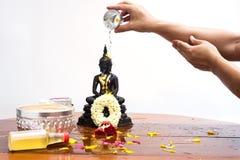 La mano vierte el agua en la estatua de Buda de la cabeza Fotos de archivo libres de regalías