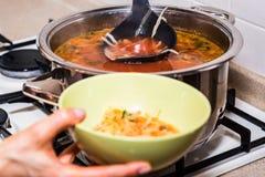 La mano vierte el borscht o la sopa de verduras roja en cuenco fotos de archivo
