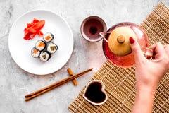 La mano vierte el té cerca de la placa con el rollo de sushi con los salmones y el aguacate en la opinión superior del fondo de p Foto de archivo libre de regalías