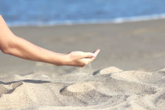 La mano vierte la arena Imágenes de archivo libres de regalías