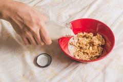 La mano vierte la leche en los cereales Fotos de archivo libres de regalías