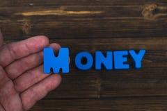 La mano y el finger arreglan letras del texto de la palabra del DINERO en la tabla de madera Imagenes de archivo