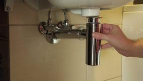 La mano y los agregados del ` s del hombre el muelle sacan con sifón el tubo con los tubos y el fregadero de alcantarilla almacen de metraje de vídeo