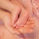 La mano y los pies recién nacidos de la madre Imagenes de archivo