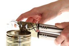 La mano y puede con el abrelatas de poder Foto de archivo libre de regalías