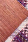 La manta de la comida campestre y el placemat tejidos del rafia modelaron el fondo Fotografía de archivo