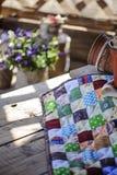 La manta hecha a mano del remiendo en la tabla de madera con la primavera florece en fondo Fotografía de archivo libre de regalías