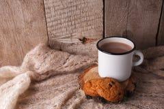 La manta hecha punto caliente, la taza de té caliente y el libro en una bandeja de madera, otoño, fondo estacional del invierno,  imágenes de archivo libres de regalías