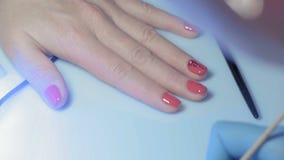 La manucure en gros plan et principale décore l'ongle sur la main de la fille avec les cailloux facettés artificiels banque de vidéos
