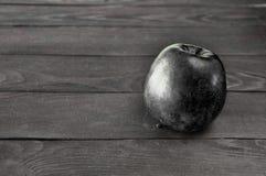La manzana negra miente en una tabla de madera gris contra fotografía de archivo