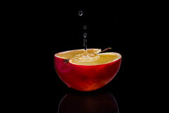 La manzana roja fresca con las gotitas del agua contra la reflexión negra del fondo cae el movimiento fresco de la acción del cha Foto de archivo libre de regalías