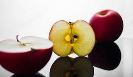 La manzana roja fresca con las gotitas del agua contra la reflexión negra del fondo cae el movimiento fresco de la acción del cha Fotos de archivo libres de regalías