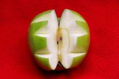 La manzana tallada en el fondo rojo, cierre para arriba/manzana del verde cortó decorativo/comida sana de las frutas y verduras Imagen de archivo libre de regalías