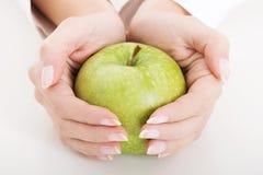 La manzana verde grande en manos femeninas hermosas Imagen de archivo libre de regalías