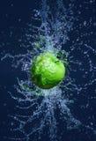 La manzana verde que vuela en agua salpica imágenes de archivo libres de regalías