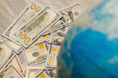 La mappa globale è un segno di molte banconote e fatture di vari stati globalmente nei dollari americani Fotografia Stock