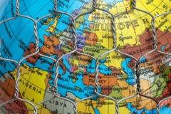 La mappa globale dietro un recinto di filo metallico Fotografie Stock