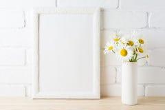La maqueta blanca del marco con la flor de la margarita cerca pintó la pared de ladrillo Imagenes de archivo