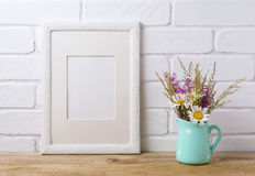 La maqueta blanca del marco con la manzanilla y el campo púrpura florece en el MI Fotografía de archivo