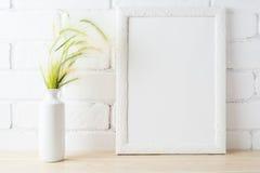 La maqueta blanca del marco con los oídos de la hierba salvaje cerca pintó la pared de ladrillo Foto de archivo