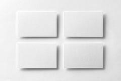 La maqueta de cuatro tarjetas de visita blancas arregló en filas en el de blanco Fotografía de archivo libre de regalías