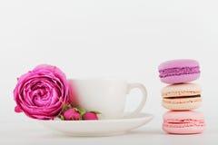 La maqueta de la taza de café con la flor color de rosa y la pila de macarrones en la tabla blanca con el espacio vacío para el t fotografía de archivo libre de regalías