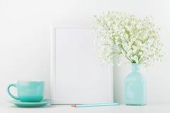 La maqueta de las flores adornadas del marco en taza del florero y de café en la tabla blanca con el espacio limpio para el texto imágenes de archivo libres de regalías