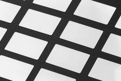 La maqueta de las tarjetas plásticas del regalo blanco arregló en filas en el pap negro Foto de archivo
