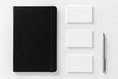 La maqueta de las tarjetas y de la libreta de visita en el blanco texturizó el backgroun Foto de archivo