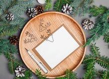 La maqueta de la tarjeta de Navidad en la placa de madera con el abeto ramifica Imagen de archivo