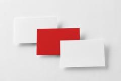 La maqueta de tres rojos y las tarjetas de visita blancas reman en el pap texturizado Fotografía de archivo