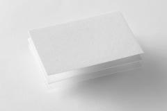 La maqueta de tres tarjetas de visita en el blanco texturizó el fondo Fotografía de archivo
