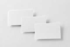 La maqueta de tres tarjetas de visita rema en el backg de papel texturizado blanco Fotos de archivo