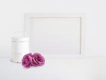 La maqueta en blanco blanca del marco de madera con la rosa vieja de la lata y del rosa florece la mentira en la tabla Diseño de  imagen de archivo