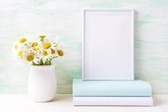 La maquette blanche de cadre avec le bouquet de camomille dans le vase rustique et huent photographie stock libre de droits