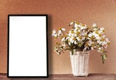 La maquette blanche vide de cadre avec la camomille fleurit dans le panier en bambou Image libre de droits