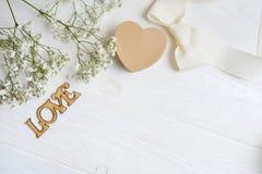 La maquette fleurit la composition d'un gypsophila blanc de cadeau avec un coeur et un amour d'inscription sur le fond en bois bl Images stock