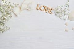 La maquette fleurit la composition d'un gypsophila blanc de cadeau avec un coeur et un amour d'inscription sur le fond en bois bl Photo libre de droits