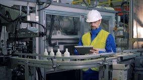 La maquinaria que transporta los buques plásticos está siendo examinada por un trabajador de sexo masculino almacen de video