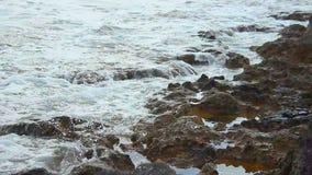 La marée ondule sur le rivage rocheux, littoral pierreux de calme, paysage tranquille, méditation banque de vidéos