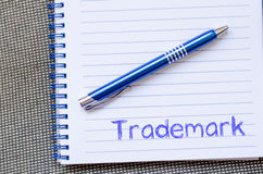 La marca registrada escribe en el cuaderno Imagen de archivo libre de regalías