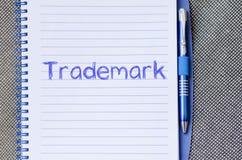 La marca registrada escribe en el cuaderno Foto de archivo libre de regalías