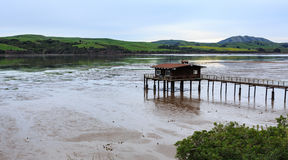 La marea baja en el muelle largo con la vertiente grande extiende hacia fuera en la bahía para atracar los barcos de pesca y clas Imagen de archivo libre de regalías