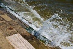 La marea del mar del oc?ano que se romp?a sobre la alga marina de piedra cubri? pasos imagen de archivo