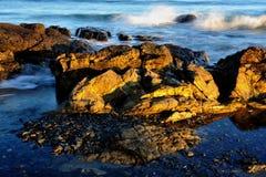 La marea inferior oscila en la costa de Nueva Inglaterra en la puesta del sol Imagen de archivo libre de regalías