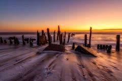 La marea saliente se lava alrededor de vieja defensa de mar en el punto Spurn Imagen de archivo libre de regalías
