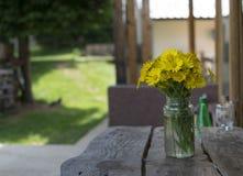 La margarita amarilla florece en florero en la tabla de madera Imagen de archivo